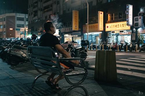 某晚在外散步,見到這位大哥獨自一人坐在長椅上抽菸,一口接著一口,吞雲吐霧外便是靜靜的望著遠方,我趕緊拿著相機開始拍了起來,一連拍了幾張都沒有我要的感覺,而這位大哥似乎也感受到我的心聲,前前後後足足抽了三根,讓一旁的我拍個夠才離去。哥抽的是寂寞不是菸,雖想自作多情的替這張照片下標,但實際上應該是家裡不能抽只好在外面抽個夠。