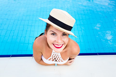 beautiful young woman in hat at the edge of the pool