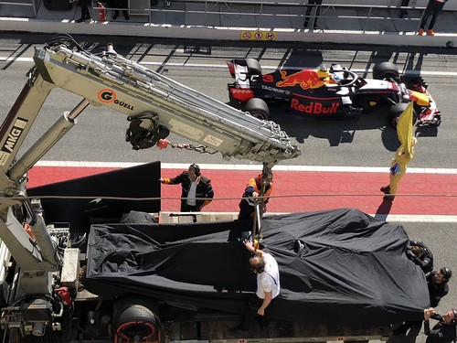 Red Bull passes the rescued McLaren as it returns to the garage at Formula One Winter Testing