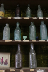 Bottles that Carpenter has collected, fill shelves near where they used to serve ice cream.