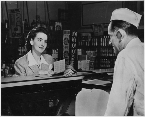 "A Customer Can Use the Ration Books of the Whole Family. But the First Thing She Will Want to Know When She Buys Pork Chops, Pound of Butter or a Half Pound of Cheese Is - ""How Many Points Will It Take?"" 1941 - 1945"
