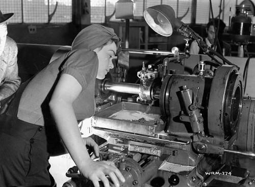 """Veronica Foster, an employee of John Inglis Co., known as """"The Bren Gun Girl"""", inspects a lathe at the John Inglis Co. Bren gun plant. / Veronica Foster, une employée de la société John Inglis Co. Ltd. connue sous le nom de « la fille au fusil mitrailleur"""