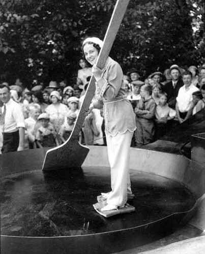Woman with slabs of bacon tied to her feet standing in a giant skillet holding an enormous wooden spatula and smiles at the crowd, Chehalis, Washington