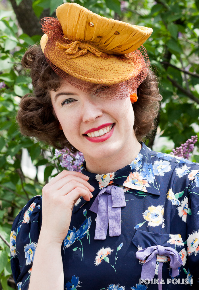 Carnation print 1930s or 1940s dress with periwinkle bow details paired with a yellow tilt hat covered in gold sequins