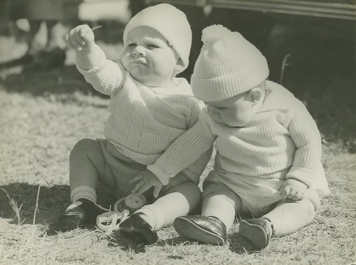 Two little babies sitting on the grass, each wearing caps and warm jumpers
