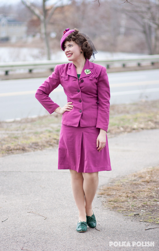Pink 1940s suit and hat paired with green shoes and blouse