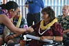 Jobie Masagatani, chair of the Hawaiian Homes Commission, presents the house key and the house plans to the recipient of Model Home #50, Luana Dang, at the dedication ceremony.