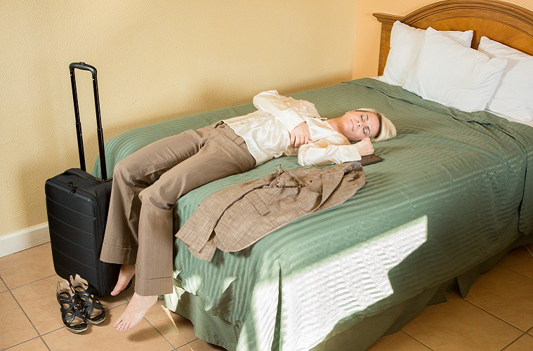 Young Businesswoman passed out asleep on a hotel bed
