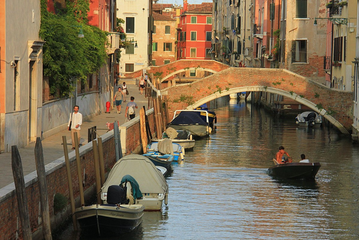 Boats floating under the bridges in Venice