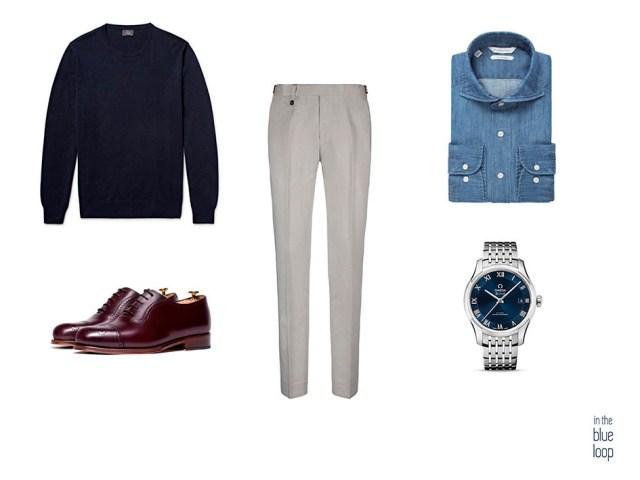 Look smart-casual masculino con pantalón de vestir, camisa vaquera, jersey azul, zapatos oxford y reloj omega