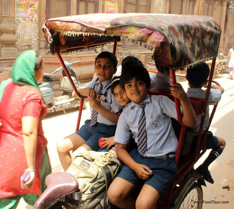 Local children on a rickshaw posing for pictures