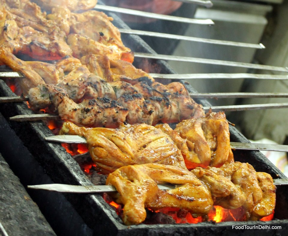 Meat kababs and tikkas being cooked over charcoal fire