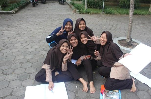 Senyum polos para siswa yang tengah menggambar di halaman terbuka sekolah