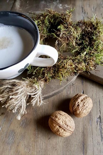 Mok koffie, houten plank en walnoten