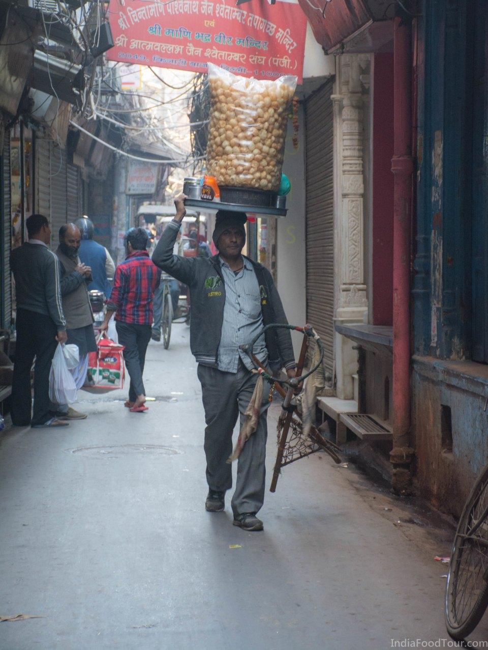 A Golgappa vendor walking through Kinari Bazar