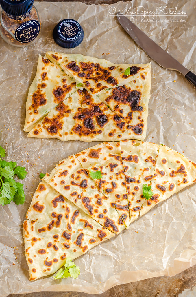patatesli gozleme cut into wedges on a wax paper.