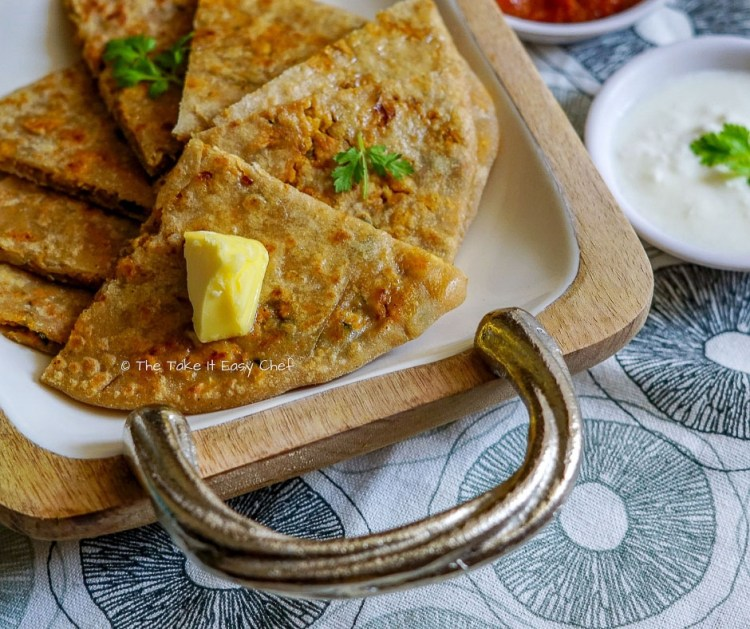 Picture of keema paratha served with pickle and yogurt