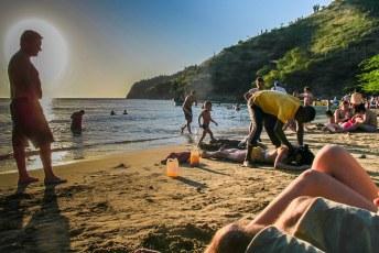 De man links, met de grote neus, kijkt argwanend toe hoe zijn vriendin wordt gemasseerd door de strandmasseur.