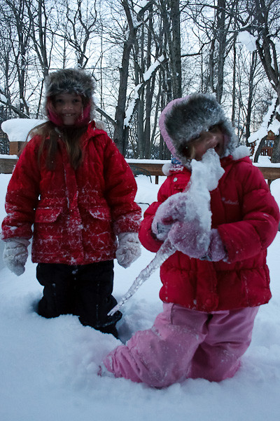 The little one enjoys an icicle, the ultimate snowy treat.