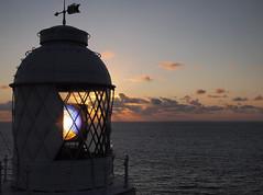 Lighthouse beam at sunset