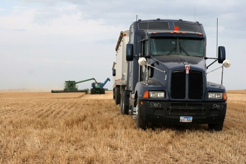A combine dumps on the graincart while the truck is lined up and ready to be dumped on.