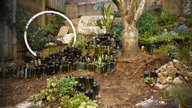 bottles rearranged to create a tiered glass retaining wall