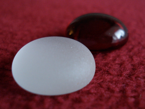 A white and dark glass gem, used as marking stones for the game Zendo.