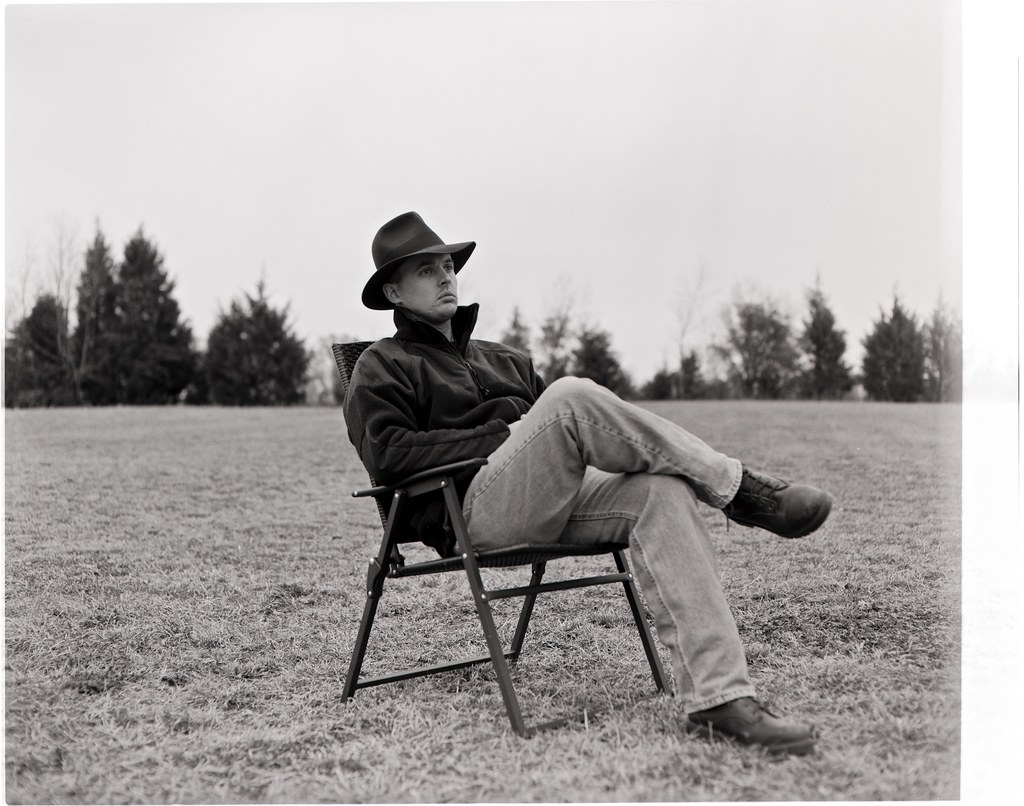 my brother tom sitting in a chair in a field