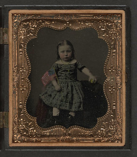 [Unidentified girl in dress holding American f...