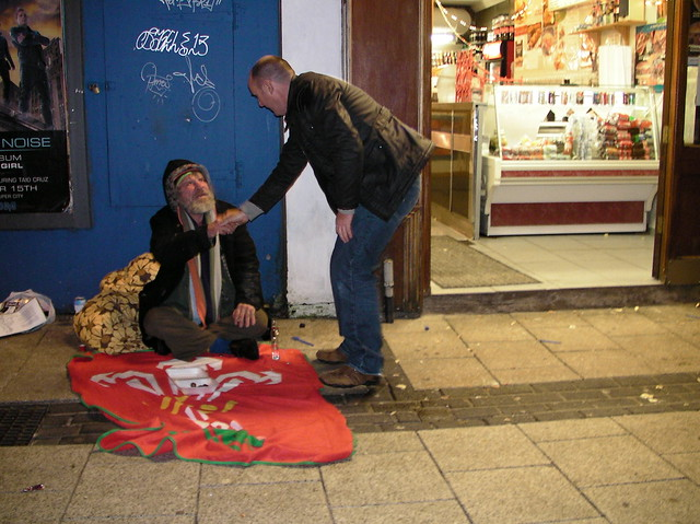 Passer by chats to homeless person