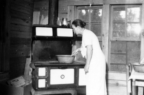 Woman cooking on a wood cook stove in a house ...