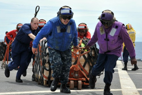 USS Blue Ridge Sailors move humanitarian relief supplies while enroute to Japan following earthquake.