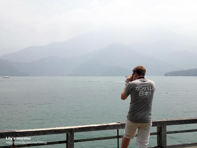 尼正拿著相機拚命拍下美麗的日月潭風光,如果那天天氣更好一點,有藍天白雲的話就更棒了。