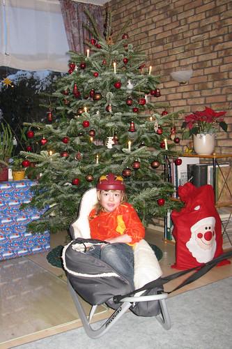 Saskia im Schlitten unterm Weihnachtsbaum