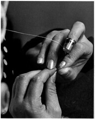 Close-up of a woman's hands threading a needle...