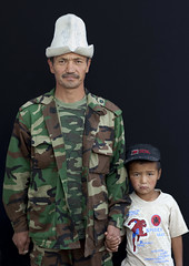 Father With Kalpak Hat And With His Son Wearing A Cap, Kochkor Animal Market, Kyrgyzstan