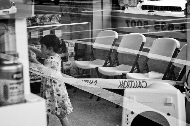 young girl playing in a pharmacy with caution tape