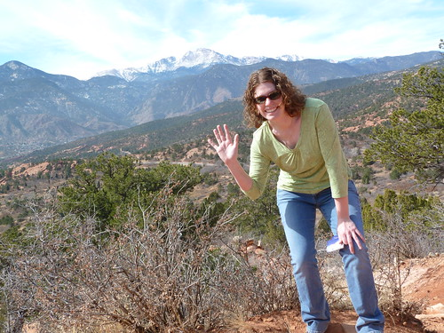 Amy waves from Garden of the Gods with Pike's Peak in background