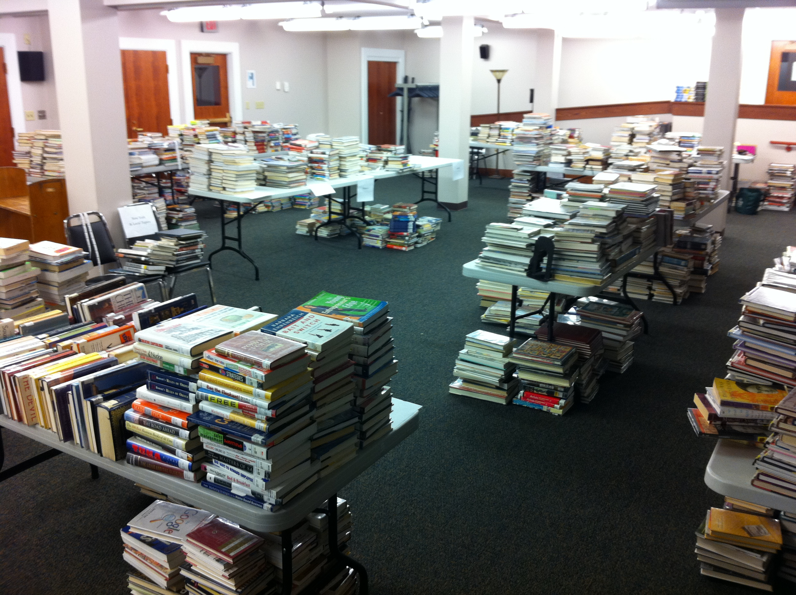 Stacks of nonfiction books waiting to be processed during the move to Dewey-free.
