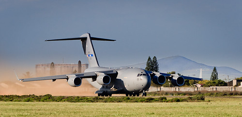 A C-17 Globemaster kicks up dust as it gathers speed in its take-off run