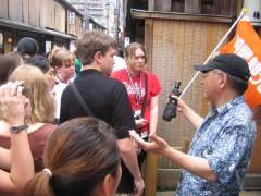 A Japanese tour guide in front of a group of Americans