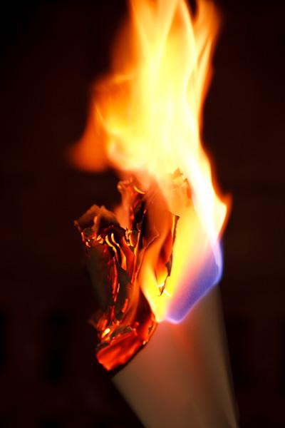 A bundle of papers begins to burn down.