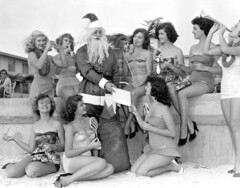 Santa Claus Giving Treats to Young Women on the Beach: Saint Petersburg, Florida