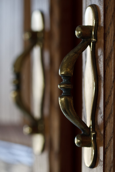 A pair of worn brass cabinet handles.