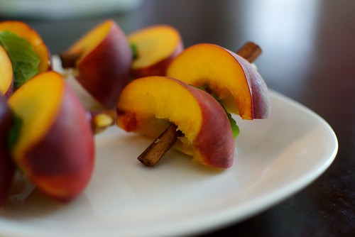 grilled peaches with mint on cinnamon sticks with bourbon sauce
