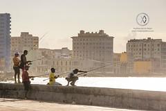 Men fish at sunset on Havana's Malecon boardwalk.