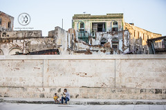 Father and son sit on a Havana street.