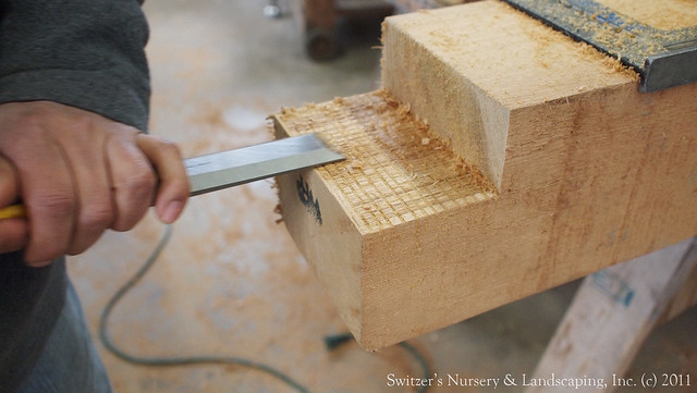 Using  a wood chisel to finish cleaning out the notch of a Real Cedar post for a Custom Classic Cedar Pergola.