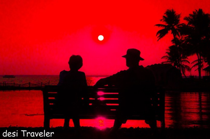 couple on bench enjoying sunset lake vembanad kumarakom lake resort