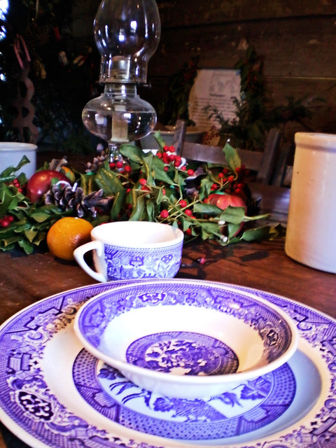 blue and white china place setting on table decorated for Christmas